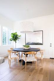 airy dining nook black table and wood chairs modern pendant light