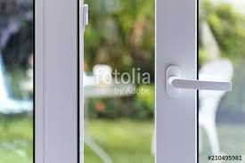 open door of a family home close up of the lock on the sliding door with the yard of background white pvc door and double glass