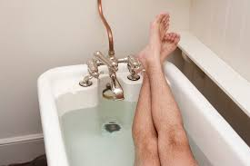 cropped view of a man relaxing having a bath with his feet resting up on the