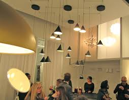 flos lighting soho. superloon is a minimally designed, flat disc lamp mounted on gyroscopic axis atop three-legged stand. the moon-inspired light surface for which flos lighting soho s