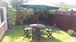 garden wooden table and chairs with parasol and cushions