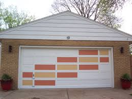 various rectangular panels on a white garage door have been painted two shades of orange
