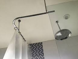 corner shower curtain rod with a suspended end used with white open top shower hooks