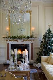 crystal drop chandelier above coffee table with lit fire and tree in kent country house