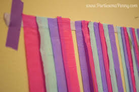 to add some pieces of fringe fold up a strip of the streamer leaving at least 1 inch of space to secure it to the sticky masking tape