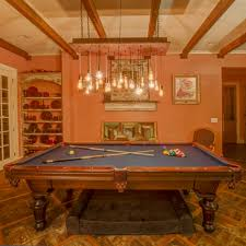multi pendant chandelier hanging over a pool table