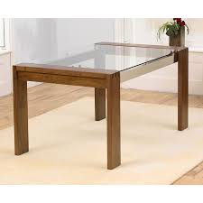 dining room rectangle glass top table with four brown wooden legs on the cream rug