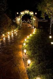 cafe bulbs light the path to a decorated arch at this outdoor evening wedding reception