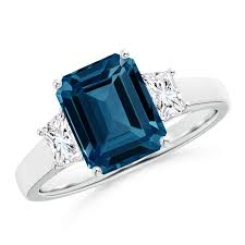 symbolizing the past present and future of your relationship this three stone ring is studded with an emerald cut london blue topaz and two tzoid