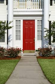 entry door kick plates. the entry, a six-paneled door, is red and has bronze kick entry door plates