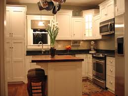 white theme small kitchen with black countertop also tiny kitchen island and rounded stool