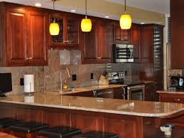 traditional kitchen with brown granite countertop design orange hue luma pendant kitchen lights and solid wood bar stools black cushion