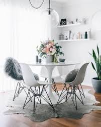 dining room decor ideas small modern style dining with white and grey color palette white round table eames chairs cowhide rug floating shelves and