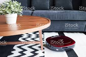 Robot vacuum cleaner cleaning the floor in cozy living room. royalty-free  stock photo