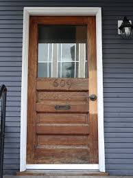 wooden front doors with glass brown door on the top placed gray wall leaded