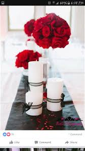 White candles with black ribbon and red flowers for dramatic centerpieces