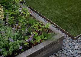 in brooklyn garden designer julie farris uses metal landscape edging and river rocks to border