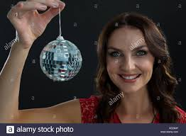 Portrait of smiling woman holding mirror ball against black Stock