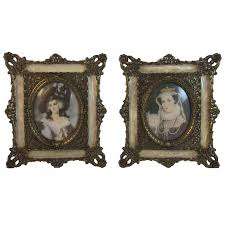 pair metal filigree frames with celluloid faux mop embellishment and miniature prints of paintings of queens