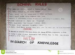 a sign with the school rules is hanging on the wall of a primary school in kenya africa this school is situated in an area called loita hills