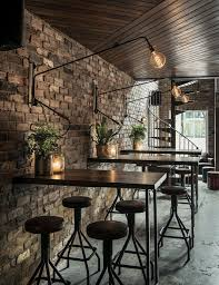 Black Chairs And Metal Tables For Cozy Coffee Shop Interior Design Ideas  With Stone Wall