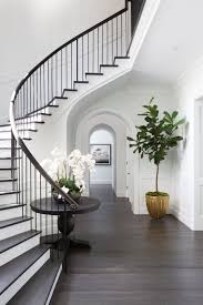 a bright foyer with dark wood floors and white walls archdigest