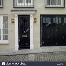 black front door and garage door of residential house opening directly onto cobbled street lyall mews belgravia london uk