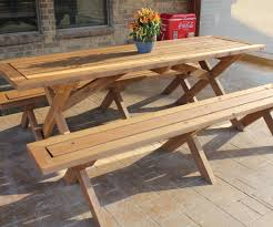 long outdoor wooden picnic table with detached benches and flower centerpieces for patio with stone floor tiles ideas