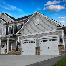 a home with an attached garage that features 2 white garage doors