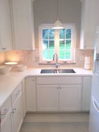 lighting over kitchen sink. white kitchen set idea with shade pendant lighting fixture over the sink k