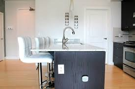 Two Armless White Leather Bar Stools At Ebony Colored Kitchen Island With A  White Marble Countertop
