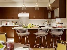 bamboo cabinets solid countertop integral sink 3 glass pendant lights round dining table and chairs white backsplash tile and vent hood small kitchen