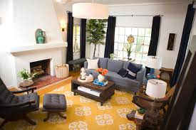 big yellow area rug living room with dark grey sofas and a grey
