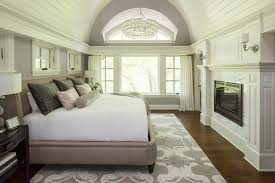 vaulted ceilings crystal chandelier glass chandelier upholstered headboard master bedroom tongue groove gray walls bedroom fireplace gray rug transom