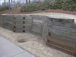 unique wood material for interesting retaining wall ideas for wide garden with green plantations