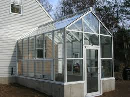 a basic white aluminum frame horticultural hobby greenhouse was attached to the home equipped with motorized roof and side vent additional awning