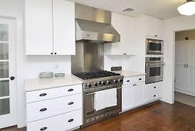 small single line kitchen with white cabinets and quartz countertops