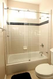 rectangle white bathtub with glass door connected by beige wall tile
