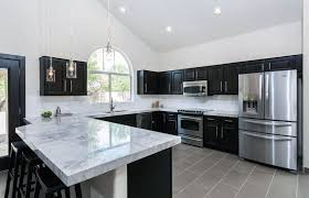 transitional kitchen with dark cabinets dining peninsula and calacatta carrara marble counter