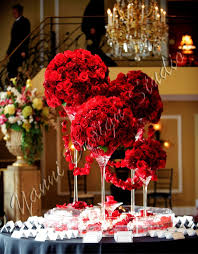 varying heights of martini glasses topped with red rose and hydrangea  arrangements in a pool of floating candles and fresh petals