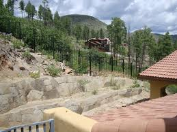 rock retaining wall with metal fence