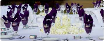 a catered wedding reception table setting with purple linen napkins and white plumeria on white linen wedding catering contract sample