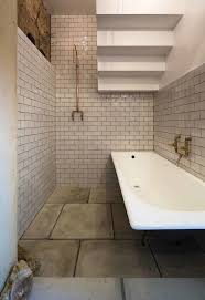 dwell bathroom cabinet: in the bathroom beneath the stairs copper fixtures and subway tile feel at once sensitive