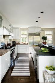 at rebecca and jon bond s hamptons home a trio of pendant lights from laurin copen antiques hangs in the kitchen which is outfitted with a sub zero