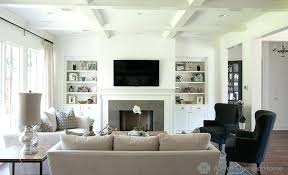 chic living room with bookshelves and cabinets filling alcoves on either side of fireplace shelves each design fill nooks fi