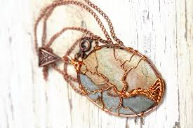 a multicolor cabochon agate is encircled in copper and a tree of life pendant is wire