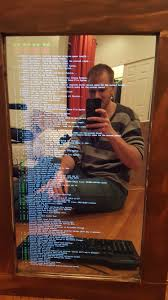 pierce sitting in front of the mirror displaying the raspberry pi boot sequence