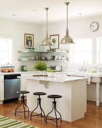 a pair of industrial pendants hang over a white kitchen island topped with white marble with plenty of overhang lined with wisteria industrial iron swivel