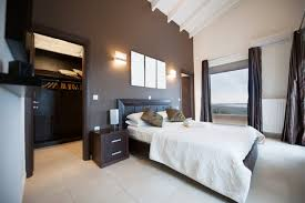 modern master bedroom with a walk in closet dark accent wall tile flooring