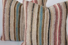 this pair of rag rug pillows are in nice country colors and have a tan cotton